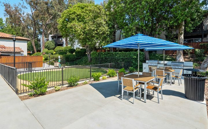 BBQ area with umbrellas and chairs near pool at Los Robles, apartments in Thousand Oaks