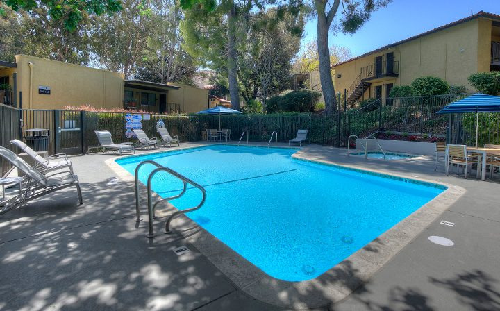 Pool with umbrellas and chairs at the Thousand Oaks apartments community Los Robles