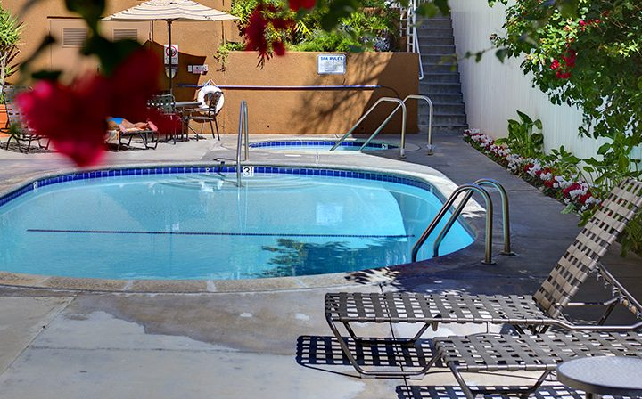 Outdoor pool next to hot tub with seating at Marlon Manor, Los Angeles apartments in Hollywood