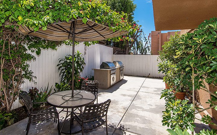 Shaded outdoor seating with BBQ grill at Marlon Manor, Hollywood apartments in Los Angeles