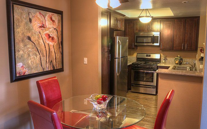 Furnished kitchen area with art and red chairs at Marlon Manor, Los Angeles apartments in Hollywood