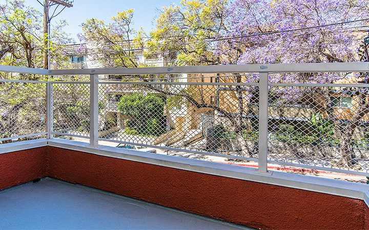 Balcony with fence overlooking blooming trees at Marlon Manor, Hollywood apartments in Los Angeles