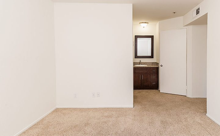 Carpeted hallway with white halls in unit at Marlon Manor, Hollywood apartments in Los Angeles