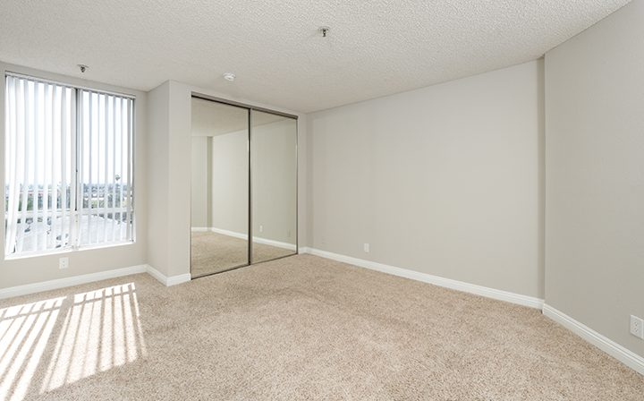 Carpeted bedroom with mirrored closet at Media Towers, Hollywood apartments in Los Angeles