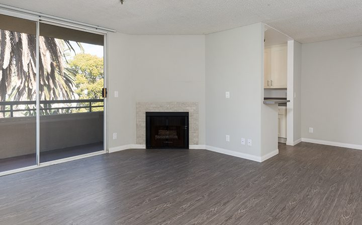 Living room with balcony and fireplace at Media Towers, Los Angeles apartments in Hollywood
