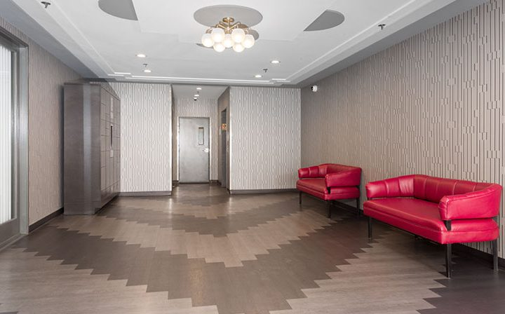 Patterned floor in lobby with red couches at Media Towers, Hollywood apartments in Los Angeles