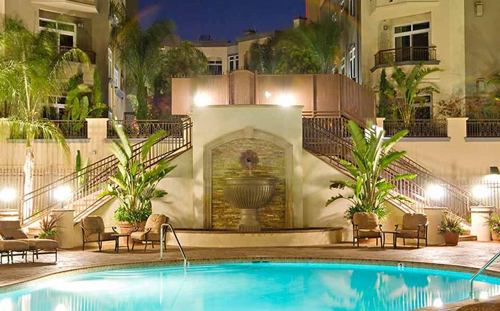 Nighttime view of Silicon Beach apartment Playa del Rey ornate pool area with planted palm trees