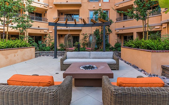 Outdoor sitting area and BBQ pits at Silicon Beach apartment community Playa del Oro