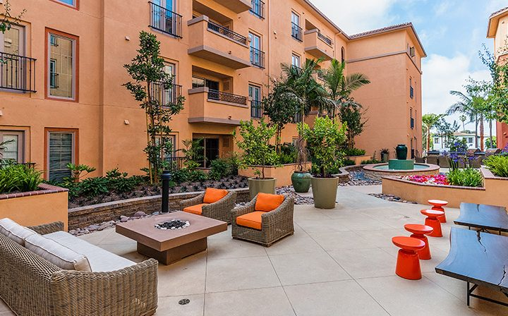 Outdoor seating with orange accents and barbecue pits at Playa del Rey apartment community
