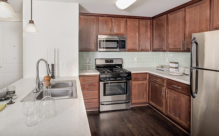 Playa del Rey apartment Playa del Oro kitchen with breakfast bar, tiled backsplash, and microwave