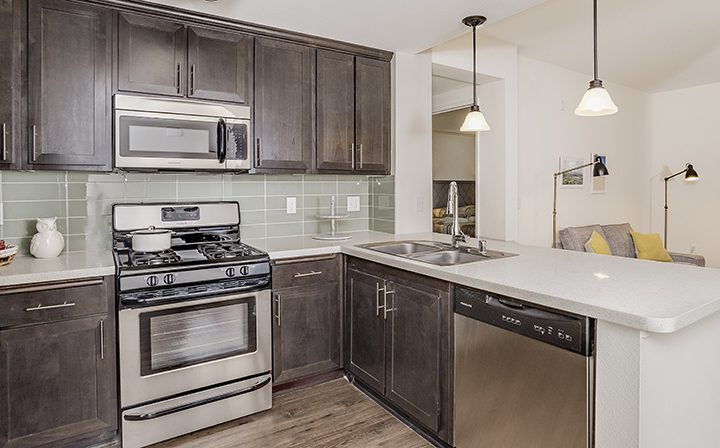 Silicon Beach apartment Playa del Oro kitchen featuring built in microwave and tiled backsplash