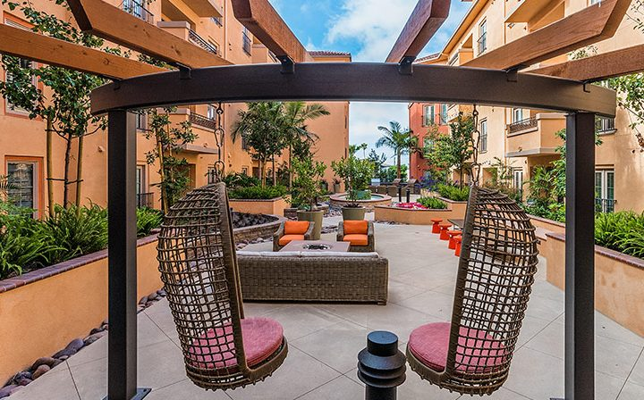 Wicker swing seats in outdoor seating and BBQ area at Silicon Beach apartment complex Playa del Oro