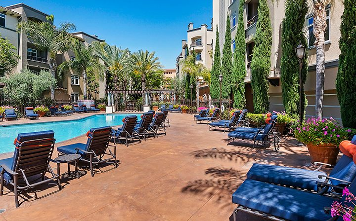 Poolside with seating at the Playa del Rey apartments community Playa del Oro
