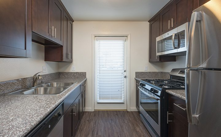 Sink adjacent stove and brown cabinets at Playa Marina, Playa Vista apartments in Los Angeles