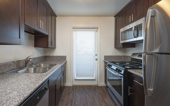 Sink adjacent stove and brown cabinets at Playa Marina, Playa Vista apartments in Los Angeles