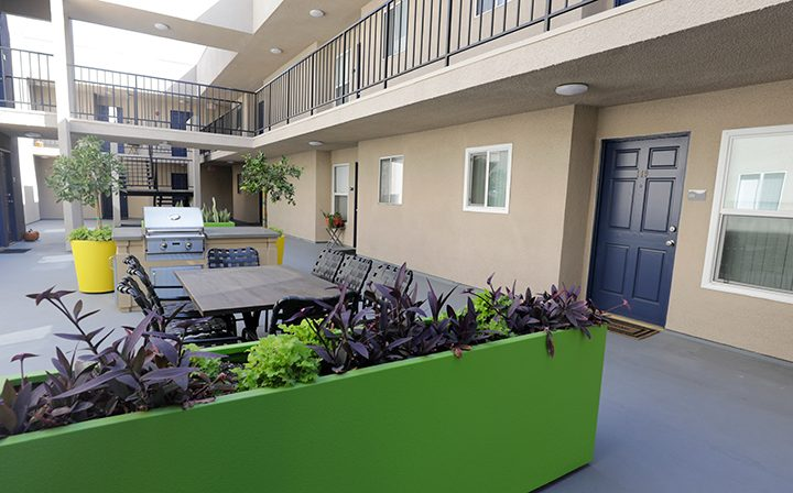 Colored planters outside blue-doored units at Playa Marina, Los Angeles apartments in Playa Vista