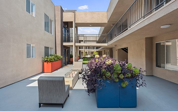 Courtyard with colored planters and seating at Playa Marina, Playa Vista apartments in Los Angeles