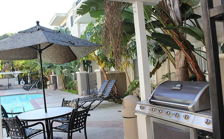 BBQ grill near seating and pool at Playa Pacifica, Los Angeles apartments in Playa del Rey