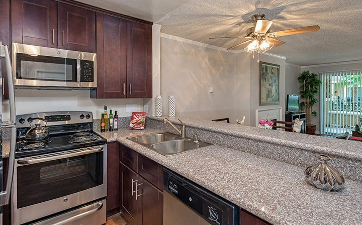 Furnished kitchen with brown cabinets at Playa Pacifica, Playa del Rey apartments in Los Angeles