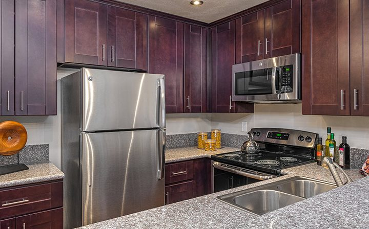 Furnished kitchen with brown cabinets at Playa Pacifica, Los Angeles apartments in Playa del Rey