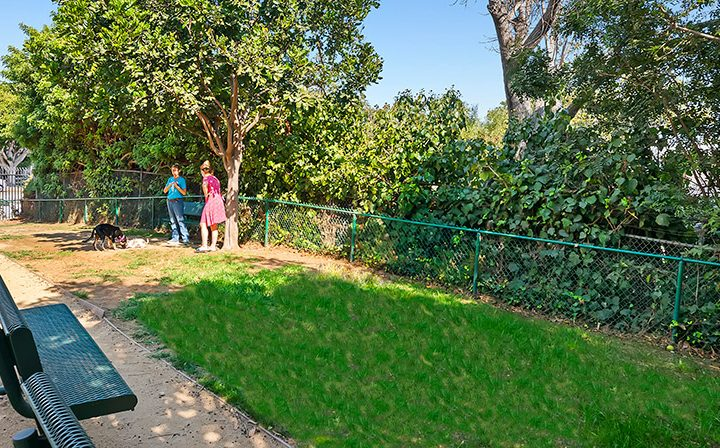 Grassy dog park area with benches at Playa Pacifica, Playa del Rey apartments in Los Angeles