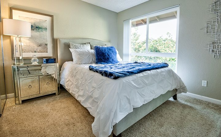 Furnished bedroom with large, bright window at Rancho Luna Sol, Bay Area apartments in Fremont