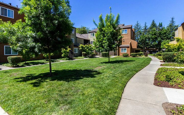 Grassy grounds with path between apartments at Rancho Luna Sol, Bay Area apartments in Fremont