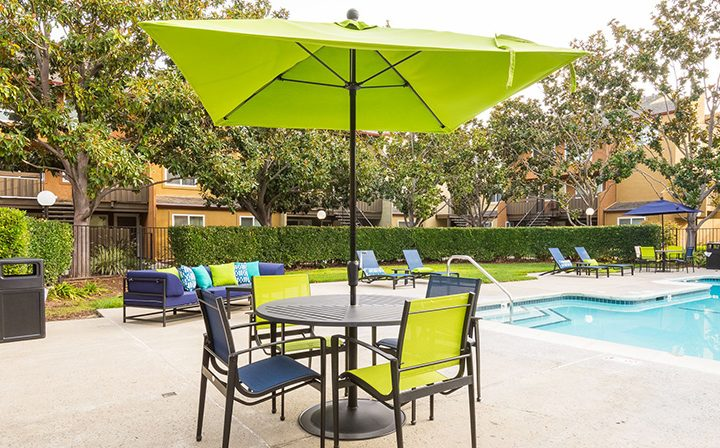 Lime green umbrella and chairs by pool at Rancho Luna Sol, Fremont apartments in the Bay Area