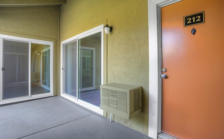 Entrance to orange-doored unit with yellow wall at Rancho Luna Sol, Bay Area apartments in Fremont