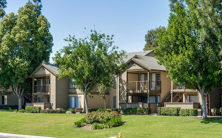 Exterior view of several Reserve at Chino Hills apartments with grassy field, trees, and shrubbery