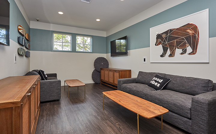 Recreation room with couches, table, and television at the Reserve at Chino Hills apartments