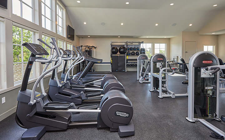 Sunny fitness room with cardio and weight machines at the Reserve at Chino Hills apartments