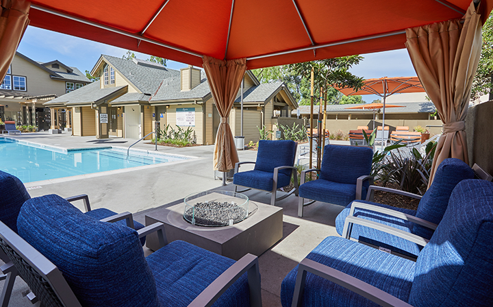 Cushioned seating under orange canopy next to large pool at the Reserve at Chino Hills apartments