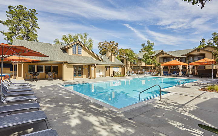 Pool outside clubhouse with seating, umbrellas and canopies at the Reserve at Chino Hills apartments