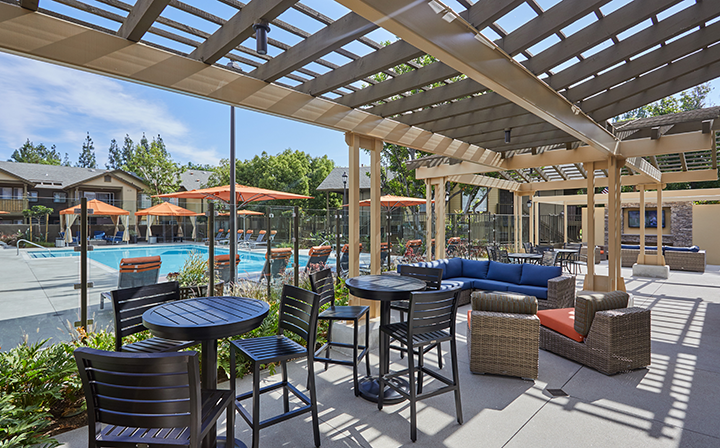 Padded seating and tall chairs in shaded area by large pool at the Reserve at Chino Hills apartments