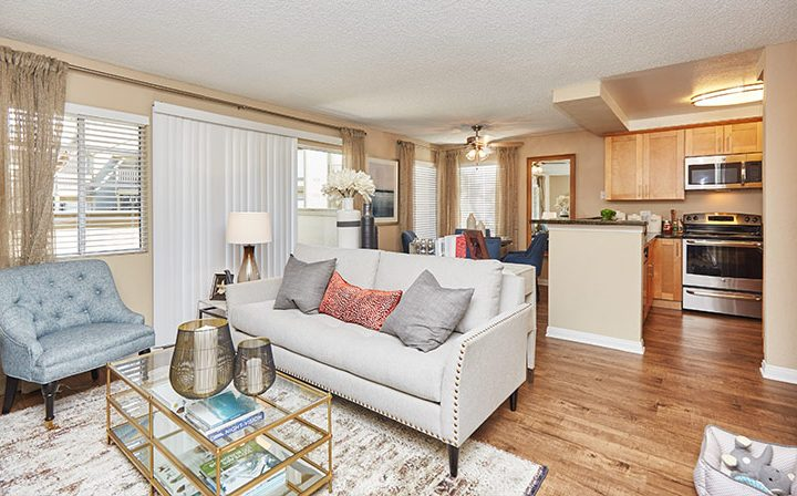 Furnished living room with kitchen and ample natural light at the Reserve at Chino Hills apartments