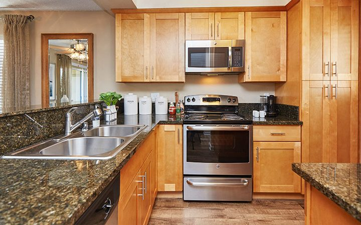 Large kitchen with stone counters, wood cabinets, and range at the Reserve at Chino Hills apartments