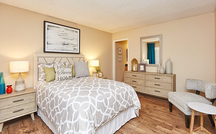 Cozy furnished bedroom with bathroom and hardwood floors at the Reserve at Chino Hills apartments
