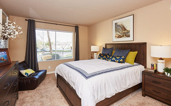 Carpeted furnished bedroom with windows for natural light at the Reserve at Chino Hills apartments