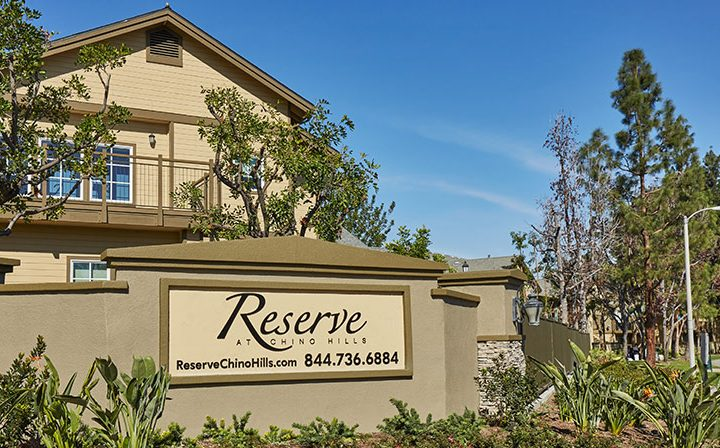 Exterior view of entrance to the Reserve at Chino Hills apartments community with sign