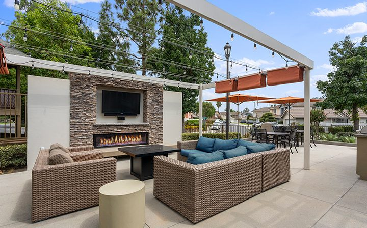 Cushioned seating in front of large outdoor flat screen TV at the Reserve at Chino Hills apartments