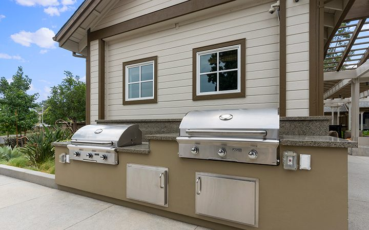 Large BBQ grills with seating near the pool at the Reserve at Chino Hills apartments