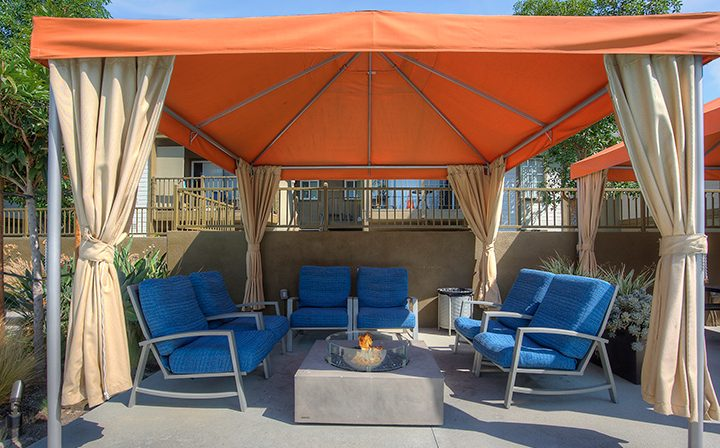 Cushioned seating under orange canopy near pool at the Reserve at Chino Hills apartments