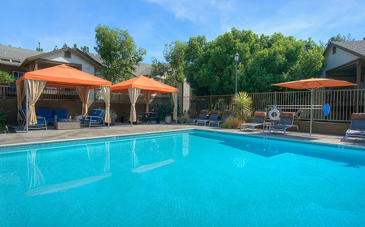 Large resort-style pool with seating and orange umbrellas at the Reserve at Chino Hills apartments