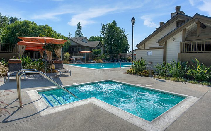 Hot tub by seating and orange umbrellas near pool at the Reserve at Chino Hills apartments