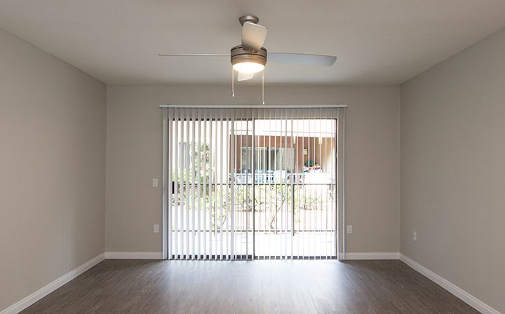 Living room interior with glass door to patio at the Reserve at South Coast apartments in Santa Ana