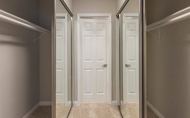 Large walk-in closet with mirrored doors and space on both sides at the Reserve at South Coast Apartments