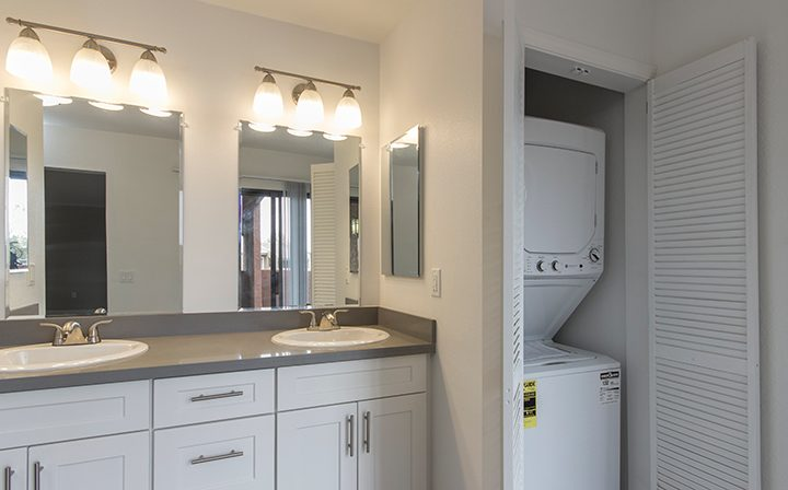 Bathroom with lighted mirrors next to in-unit washer and dryer at Adagio at South Coast apartments