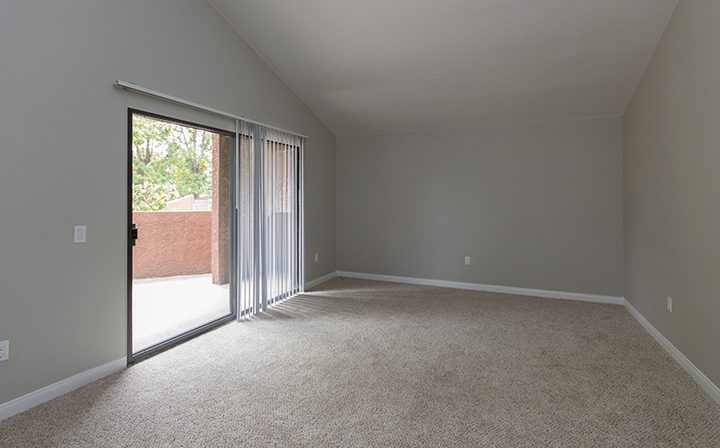 Large unfurnished bedroom at the Reserve at South Coast apartments with sunny view and balcony exit