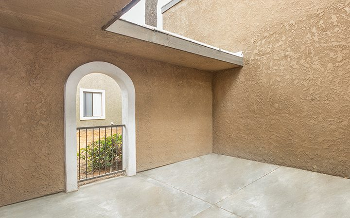 Sunny open outdoor area with stylized archway the Reserve at South Coast apartments in Santa Ana